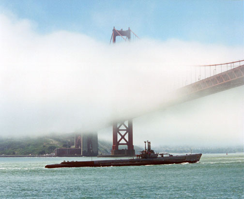 Photo of Pampanito being towed under the Golden Gate Bridge.